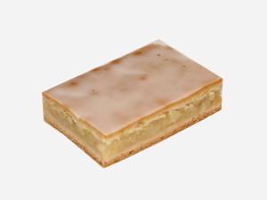 Prażone jabłka pomiędzy warstwami kruchego ciasta, całość przykryta lukrem.