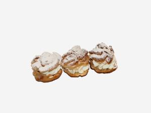 Bita śmietana pomiędzy korpusami z ciasta parzonego. Całość udekorowana cukrem pudrem.