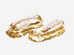 Krem budyniowy pomiędzy korpusami z ciasta parzonego. Całość udekorowana białą polewą lukrową i kolorową posypką.